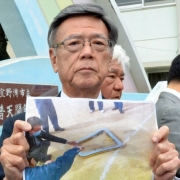 Okinawa Governor Takeshi Onaga shows the window that landed on a school sports ground last month